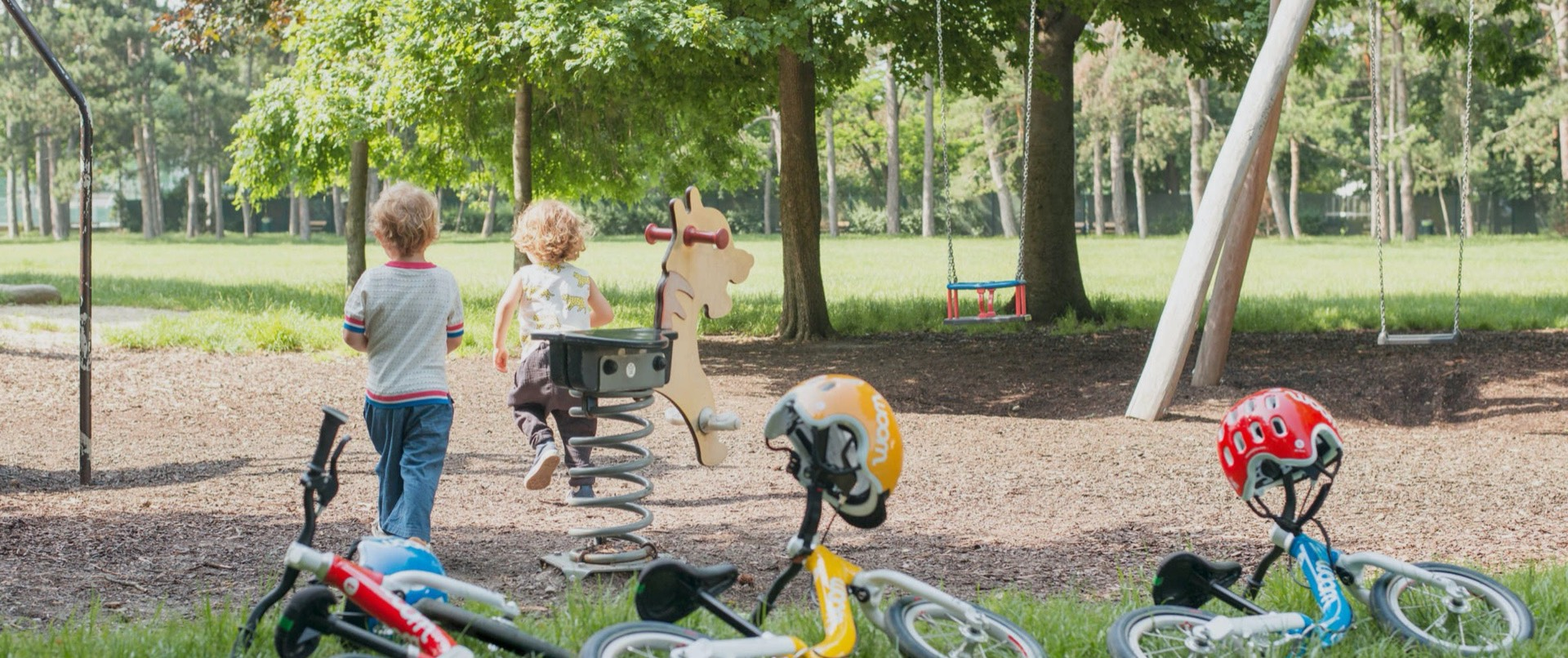 kids riding woom bikes and playing in the park