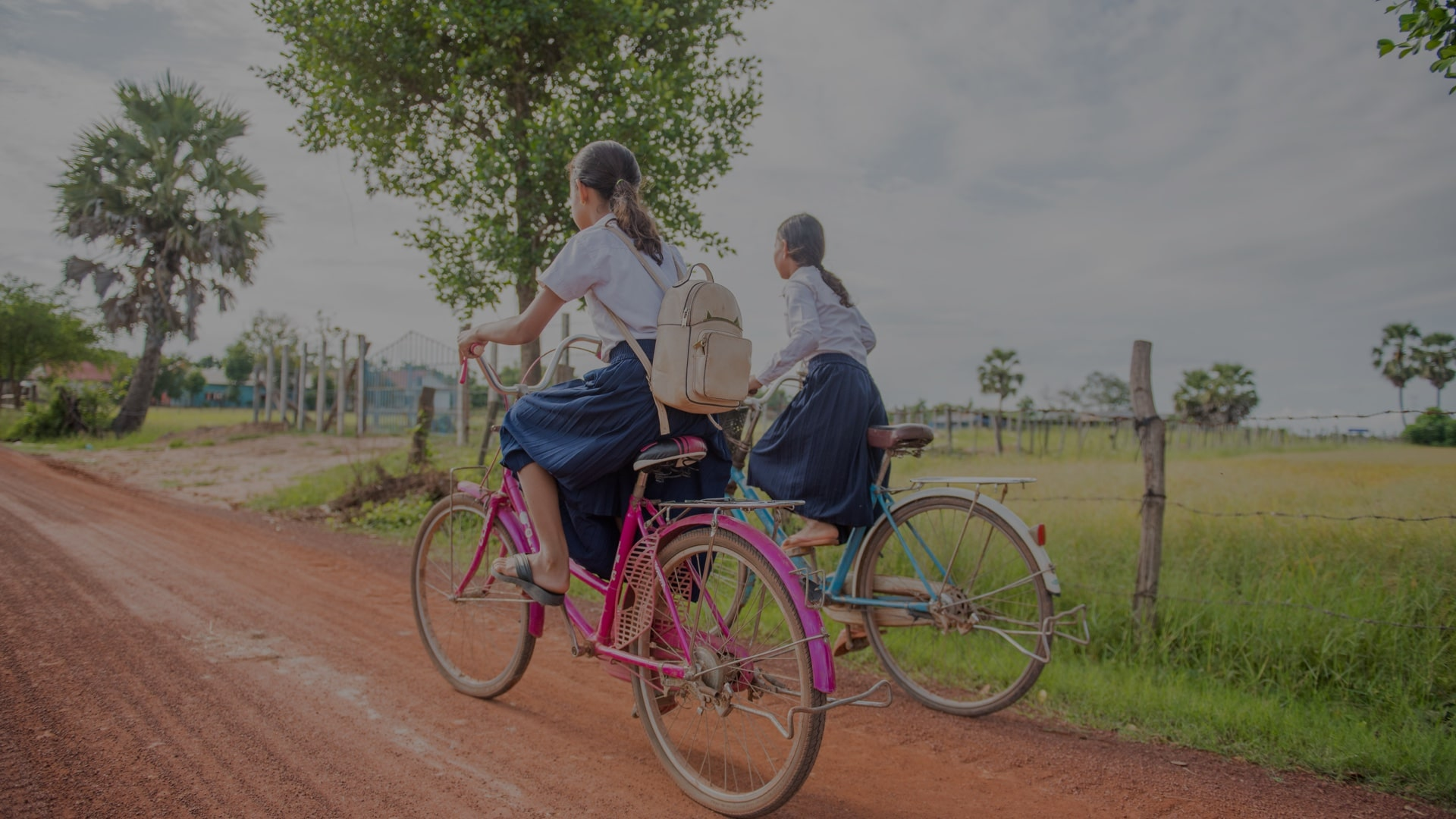 Shot from behind of two ladies riding their bikes to school